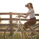 VRゴーグルをかけて自転車に乗る女性