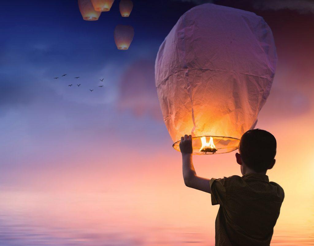 夢を詰め込んだ風船を空に飛ばす少年