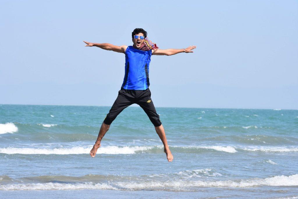 海でジャンプする男性画像